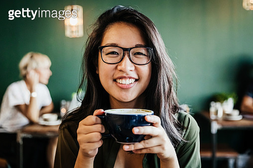 A portrait of a young Asian woman with glasses, smiling while drinking coffee in her favorite cafe. - gettyimageskorea