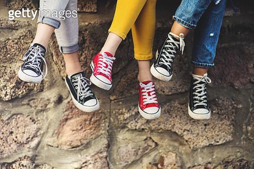 Legs of three female teenager friends sitting cross-legged on a wall, wearing sneakers. - gettyimageskorea