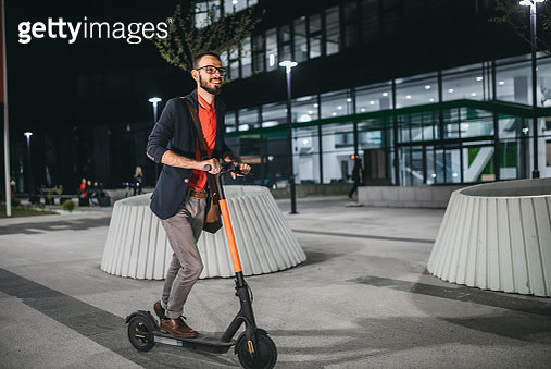 A businessman riding a scooter in the city, at night - gettyimageskorea