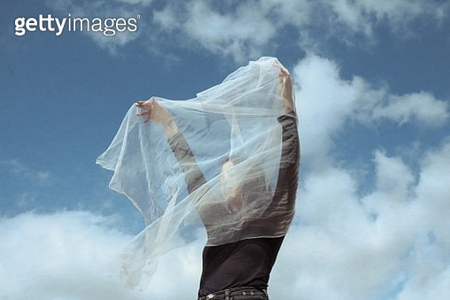 Woman Holding White Textile While Standing Against Cloudy Sky - gettyimageskorea