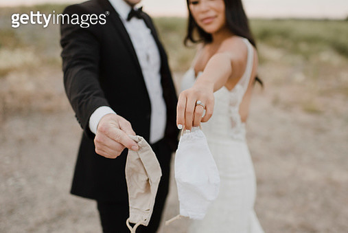 Bride with groom showing protective face mask in field during COVID-19 - gettyimageskorea