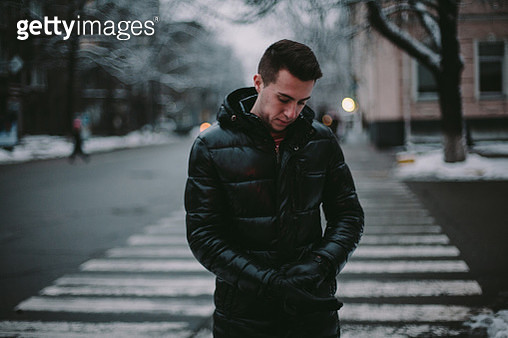 Young man wearing gloves while standing in city street during winter - gettyimageskorea