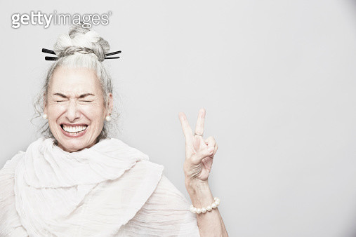 Studio portrait of sophisticated senior woman making victory sign - gettyimageskorea