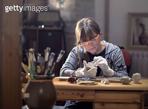 Mature middle aged hobby artist moulding raw clay in art studio - gettyimageskorea