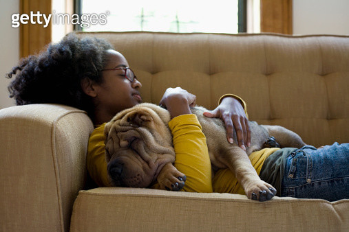 A young woman and her Shar-Pei napping on a couch - gettyimageskorea