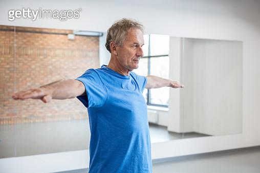 Senior man doing stretching exercise at fitness club. Elderly man having rehabilitation at health club. - gettyimageskorea