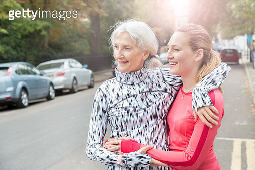 Senior woman hugs daughter after run, cityscape. - gettyimageskorea