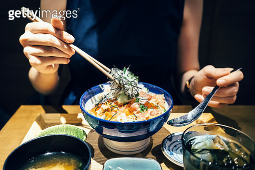 Close up of woman enjoying freshly served traditional Japanese seafood donburi with chopsticks in a restaurant - gettyimageskorea