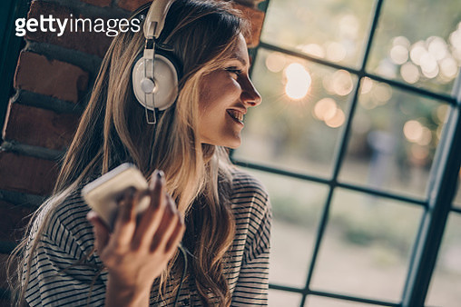 Happy woman standing by the window while listening music over mobile phone. - gettyimageskorea