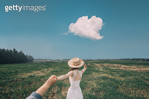 Young woman on the field holding a hand - gettyimageskorea
