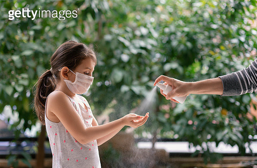 Father squirts antibacterial hand sanitizer in daughter's hands, Little girl wears a face mask during coronavirus and flu outbreak - gettyimageskorea