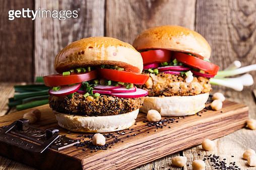 Vegan meal. Chickpea veggie burger with fresh vegetables on rustic cutting board - gettyimageskorea