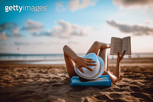 Female Reading and Enjoying Sunset on Beach by the Ocean - gettyimageskorea