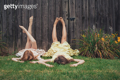 two sisters lying on the grass with their legs against the wooden fence with vintage dresses - gettyimageskorea