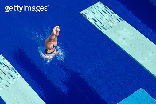 Young woman diving in swimming pool - gettyimageskorea