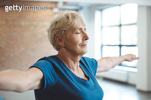 Shot of active senior woman exercising in rehabilitation centre. Elderly female doing stretching workout in health club. - gettyimageskorea