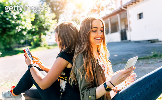 Two happy girls using their smartphones outdoors - gettyimageskorea