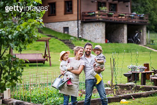 A father, mother, son and daughter standing in the garden, looking at camera. - gettyimageskorea