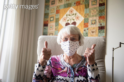 Senior woman with a home made face mask showing thumbs up - gettyimageskorea