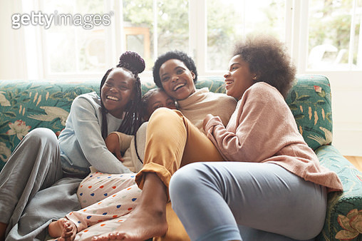 Portrait of happy young woman embracing girls while sitting on sofa at home during Christmas festival - gettyimageskorea
