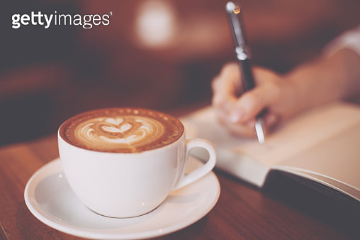 Cropped Hand Of Woman Writing On Book By Coffee On Table - gettyimageskorea