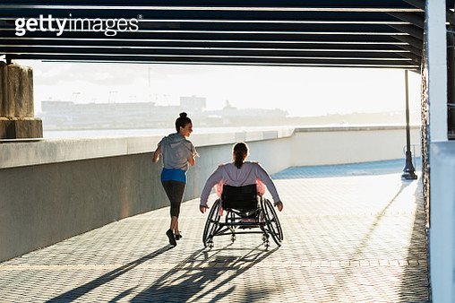 Young woman with spina bifida, Hispanic friend jogging - gettyimageskorea