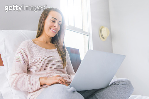 Woman working at home in bed during the COVID-19 quarantine - gettyimageskorea