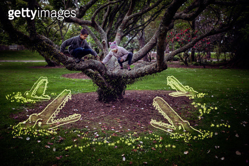 Boy and girl escape up tree away from imaginary man-eating crocodiles in the water (lawn) below. Digital composite. - gettyimageskorea
