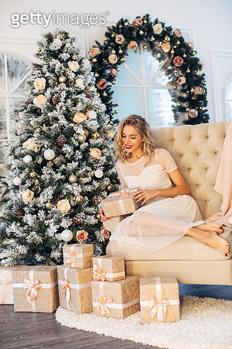 Young beautiful woman sitting next to the Christmas tree - gettyimageskorea