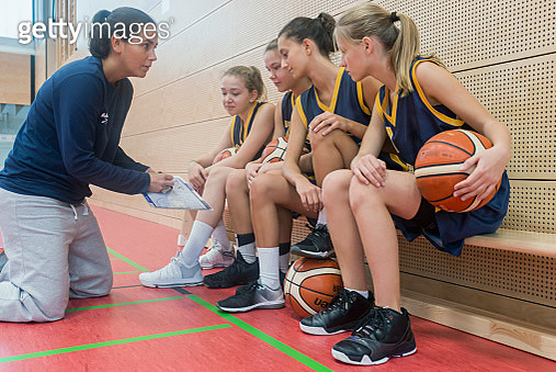 Female basketball coach teaching young players, using clipboard - gettyimageskorea