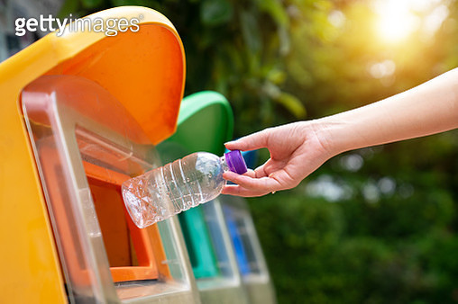 World Environment Day concept. Woman hand holding and putting plastic bottle waste into garbage trash. - gettyimageskorea