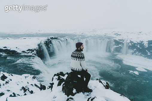 Man looking at scenic view of waterfall in winter - gettyimageskorea
