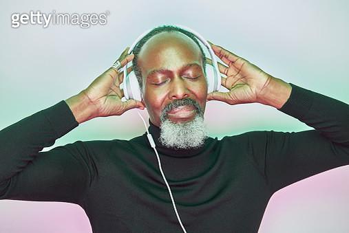 older man listening to music with headphones - gettyimageskorea