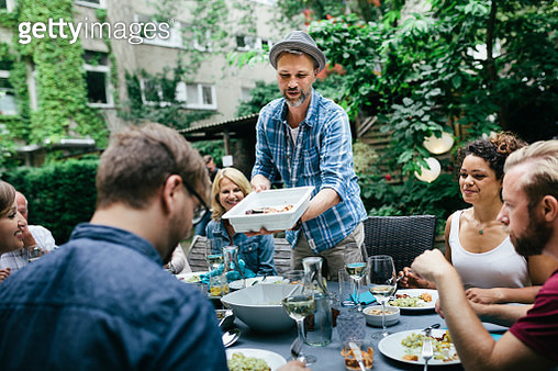 A man dishing out food to his friends at the table during a barbecue in a courtyard. - gettyimageskorea