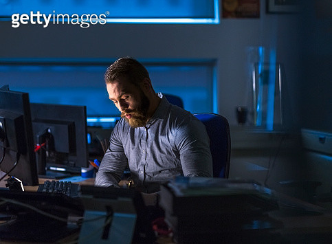 Businessman working late at computer desk - gettyimageskorea