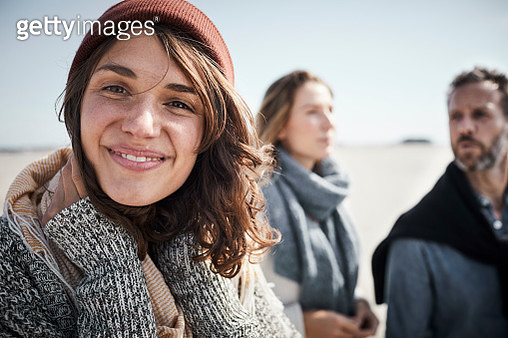 Portrait of smiling young woman on the beach with people in background - gettyimageskorea