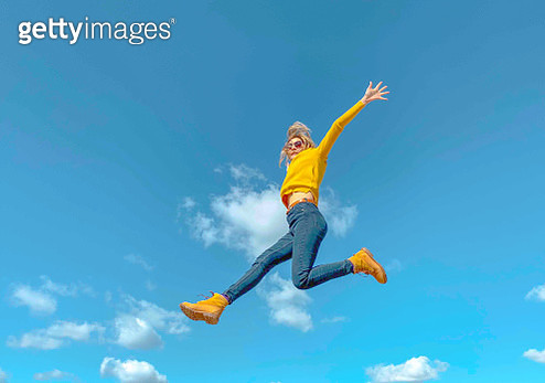 Low Angle View Of Woman Jumping Against Blue Sky - gettyimageskorea