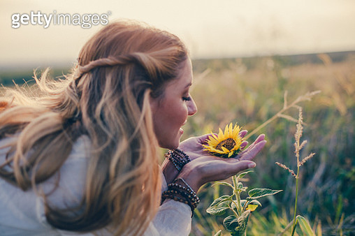 Beautiful womanl with sunflower outdoors - gettyimageskorea