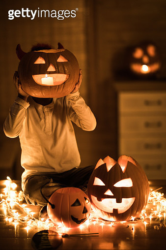 Small kid hiding his head with Jack O' Lantern on Halloween. - gettyimageskorea