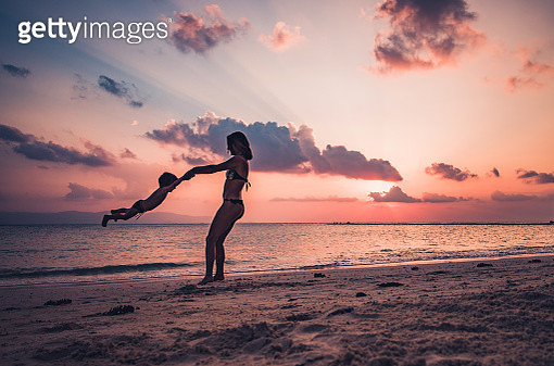 Playful mother spinning her son on a beach at sunset. - gettyimageskorea