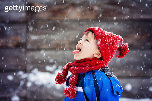 Close portrait of little boy, catching snowflakes - gettyimageskorea