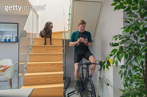 Man on cycling trainer at home - gettyimageskorea