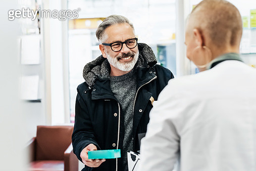 Cheerful Customer Picking Up His Prescription - gettyimageskorea