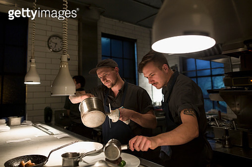 Chefs preparing food in dark kitchen - gettyimageskorea