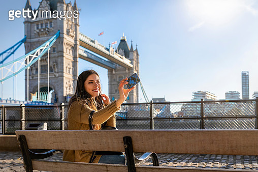 Smiling Young Woman Taking Selfie While Sitting On Bridge In City Against Sky - gettyimageskorea