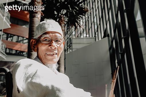 Portrait Of Smiling Senior Man Wearing Skull Cap Against Building - gettyimageskorea