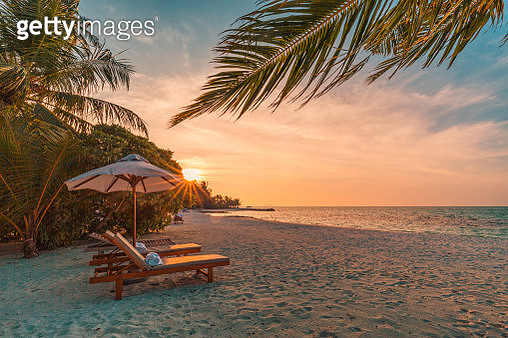 Beautiful tropical sunset scenery, two sun beds, loungers, umbrella under palm tree. White sand, sea view with horizon, colorful twilight sky, calmness and relaxation. Inspirational beach resort hotel - gettyimageskorea