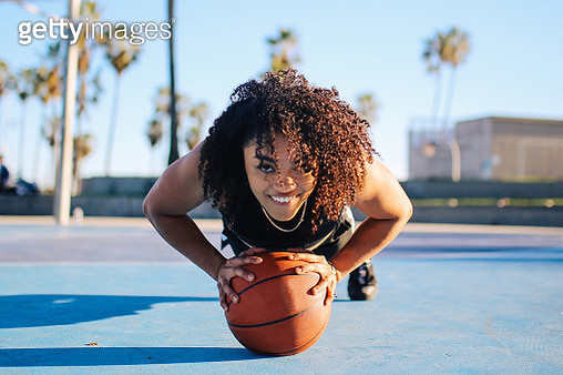 Low angle portrait of a young women doing push ups on a basketball in Venice, California - gettyimageskorea