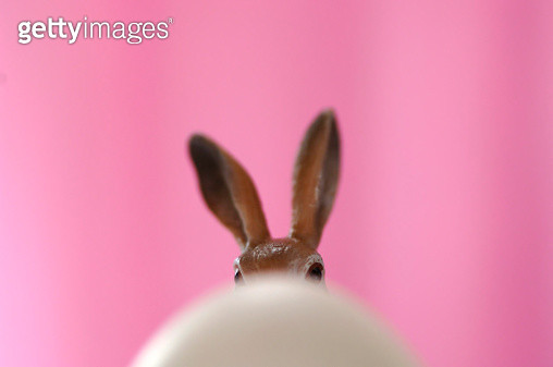 Toy Easter bunny hiding behind egg - gettyimageskorea