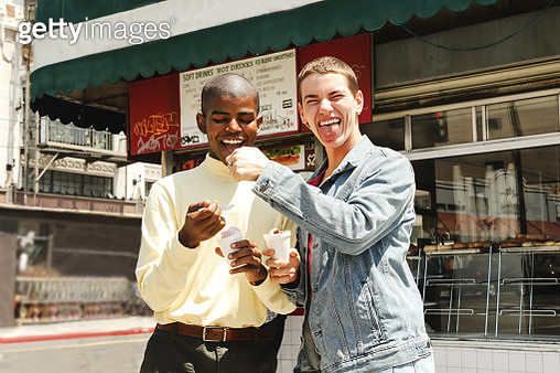 Two young males being playful while eating ice cream in front of a cafe during the day - gettyimageskorea